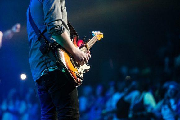 man playing guitar at a concert