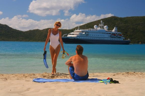 Woman and man on the beach with a cruise ship in the background